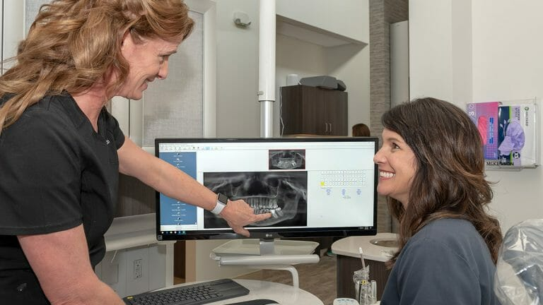 Team member showing a patient their X-rays